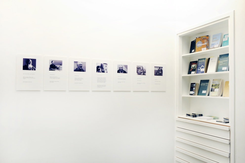 Installation view of portrait photos and titles of each individual, alongside a selection of publications related to the project